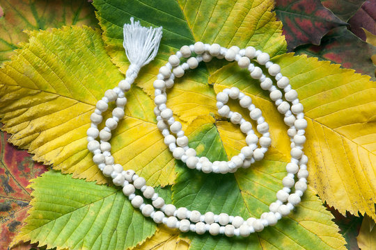 White mala rosary on the autumn leaves. Mantra. One hundred and eight beads.