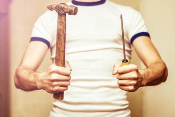 Man holding vintage hammer and screwdriver