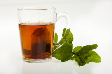 sachet de thé qui infuse dans l'eau chaude avec des feuilles de menthe