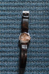 Vintage watch with leather strap on the floor