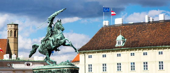 Background with horse riding statue, austrian and european flags in Vienna, Austria panoramic background
