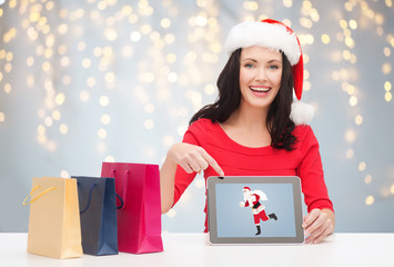 woman in santa hat with tablet pc and shopping bag