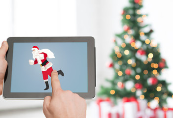 close up of hands with santa claus on tablet pc