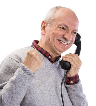 Portrait of happy senior man  talking on old landline phone