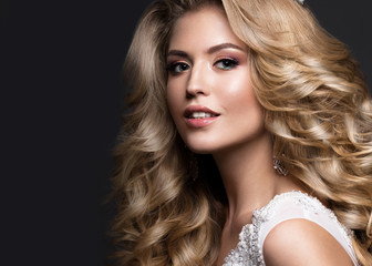 Beautiful blonde bride in wedding image with curls and crown. Beauty face. Picture taken in the studio