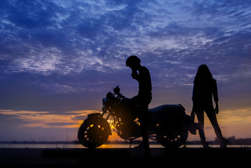 Silhouette biker and girlfriend with his motorbike beside the natural lake with sunset background.