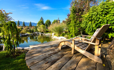 Two Adirondack chairs on a deck overlooking  pond