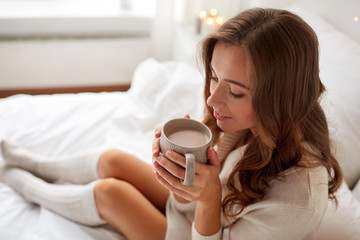 happy woman with cup of cocoa in bed at home