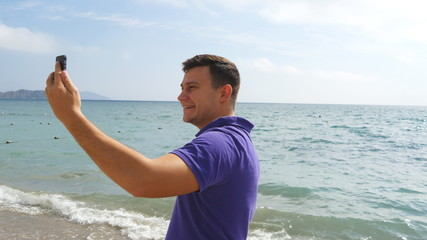 Young smiling man having a video call on smart phone at the sea beach. Happy guy making video online chats on beautiful landscape background. Boy talking on mobile and showing ocean. Man doing selfie