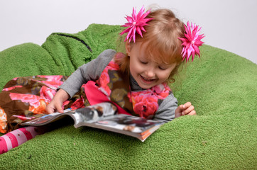 little girl lying on a bed reading a magazine