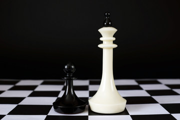 Pawn in front of enemy king. Unequal forces. Concept with chess pieces against black background