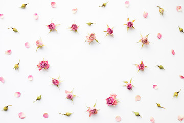 Background with shape of heart made of pink dry roses on white. Top view, flat lay, romantic card.