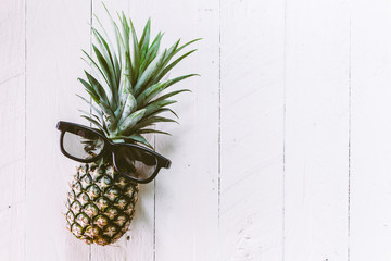 Fresh pineapple with sunglasses on wooden table