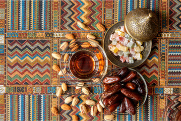 sweets, dates and tea on a traditional Arabian carpet