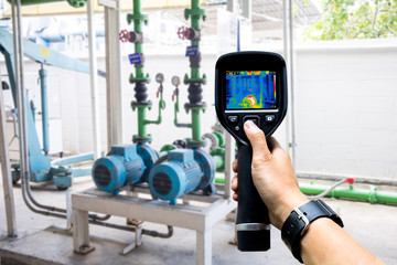 technician use thermal imaging camera to check temperature in fa