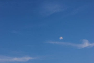 blue sky background with clouds and the moon