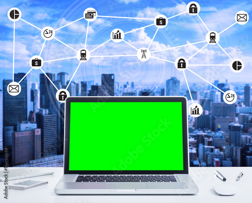 500_F_126268497_iCijmmKNHf12ZrnaVsBesfEx249lJc6r blank green screen laptop computer with night cityscape and digital