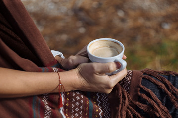 Woman hands holding cup in autumn park in morning