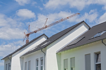 Roofs of three new terraced houses with construction crane