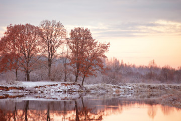 Cloudy autumn dawn. First snow on the autumn river. Oaks on rive