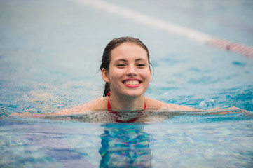 Smiling portrait of beautiful woman in swimming pool