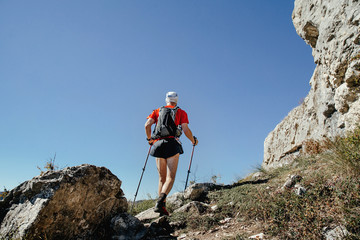 male athlete with walking poles and backpack on a background blue sky and mountains