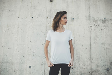 Young hipster girl wearing blank white t-shirt, stone wall background with copy space for content or design, mockup of template t-shirt, attractive woman standing against concrete wall background