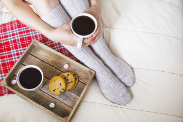 cozy Christmas at home. Christmas breakfast in bed. women's feet in warm woolen socks, two cups of coffee and chocolate chip cookies. top view. copy space for your text