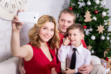 young family taking selfie photo in front of Christmas tree