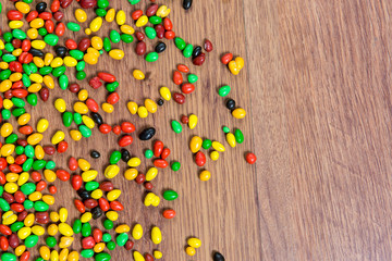 Colorful candy scattered on the wooden table.