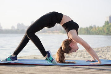 Sporty flexible girl stretches at bridge yoga exercise outdoor