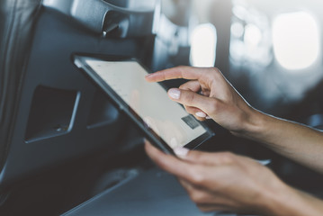 Close-up of female hands using modern digital tablet at airplane, side view of young traveler woman sitting at aircraft and reading information via portable pc