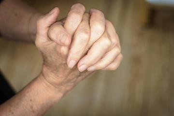 Women hands praying on wooden background