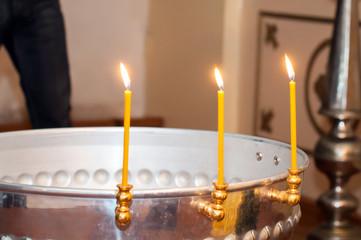 Три свечи на крестильной купели в храме