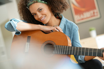 Cheerful girl playing the guitar
