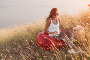 woman sitting in meadow and using her laptop.