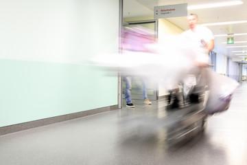 Notfallaufnahme im Krankenhaus - Angehörige folgen dem Krankenbett und Pflegepersonal