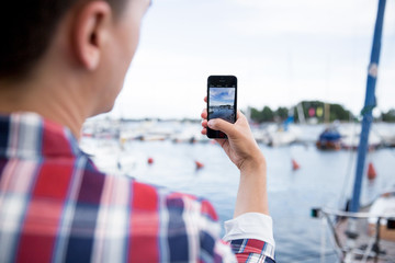 Man taking a photo with smart phone. Picture of harbor with sailboats, seaside.