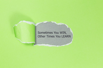The text Sometimes You WIN Other Times You LEARN, appearing behind torn paper. Motivational quote