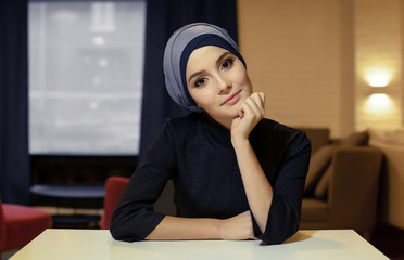 portrait of a beautiful young Muslim woman sitting at a table