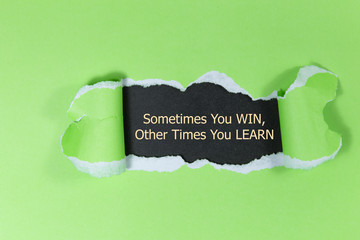 The text Sometimes You WIN Other Times You LEARN, appearing behind torn brown paper. Motivational quote.