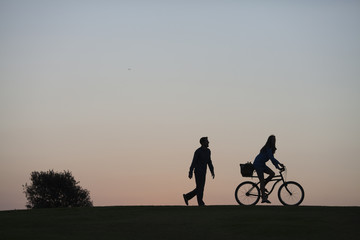 Silhouette of a couple walking through a park in San Diego at dusk. The woman is riding a bike and the man is walking.