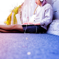 young beautiful caucasian purple grey hair woman outdoor in the city sitting on the floor listening music with head phones and computer leaning on her knee - technology, music, social network concept