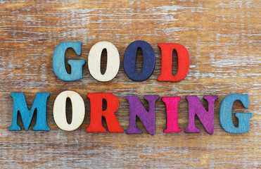 Good morning written with colorful letters on rustic wooden surface