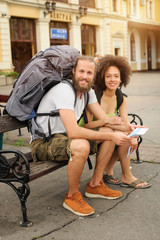 A couple of backpacker tourists sitting on a bench