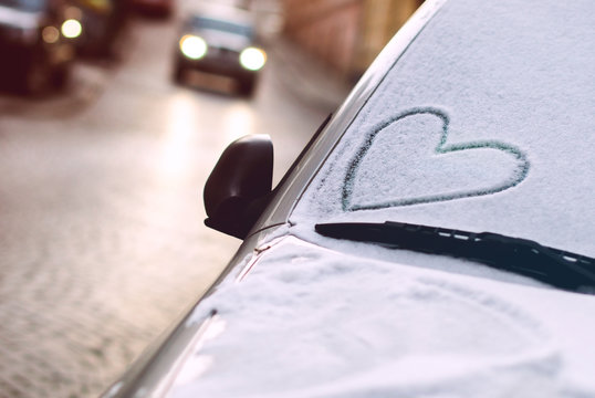 Heart drawn on a car windscreen covered with snow