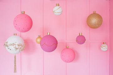 Large Christmas balls on a pink background in children room