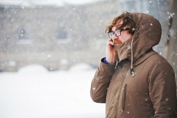 A bearded young man talking on smartphone on city street during snowfall in winter.