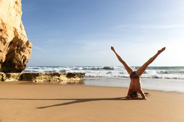 Frau macht Yoga Kopfstand Spagat am Strand, Meer