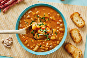 Bean soup in blue dish and wooden spoon takes bean soup